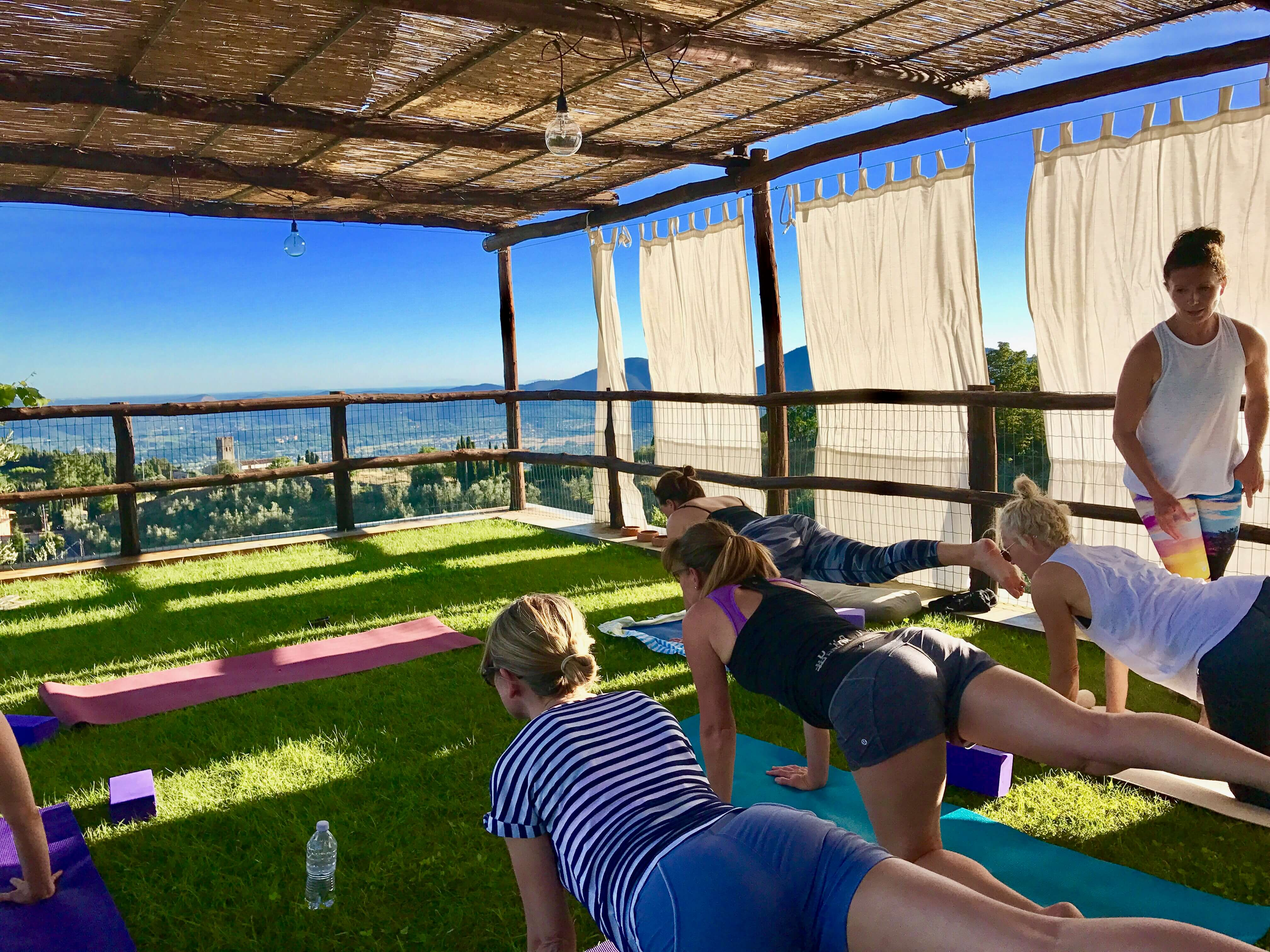 Yoga at the outdoor deck overlooking vineyards and olive groves